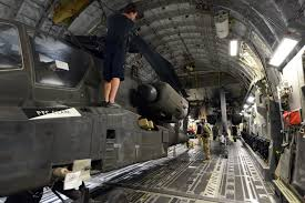 U.S. Army Spc. Byron Holmes, right, holds the rear blades of an AF-64  Apache helicopter