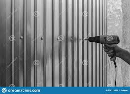 A Man Screws Sheets Of Galvanized Metal With An Electric Screwdriver Stock Photo Image Of Fence Metal 128111670