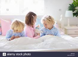 Children Play With Baby Cat In Bed In White Bedroom Kid Holding White Kitten Little Girl And Boy In Pajamas With Cute Pet Animal At Home Kids Play Stock Photo Alamy
