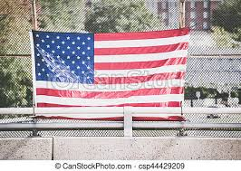 Front View Of American Flag On Fence On Blurred City Background