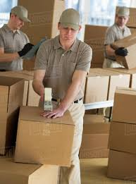 USA, New Jersey, Jersey City, men packing boxes in warehouse ...