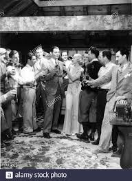 CLARK GABLE CAROLE LOMBARD Director WESLEY RUGGLES (in plus fours) with  movie crew drinking Coca-Cola on set candid during filming of NO MAN OF HER  OWN 1932 Paramount Pictures Stock Photo -