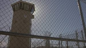 Pan Up Of Chain Link Fence With Barbed Wire On Top See Guard Tower And Prison Yard As Camera Moves Over Fence Camera Continues To Move Close To Entrance Gate See Swat
