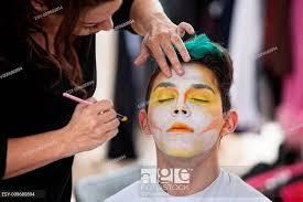 sylist putting makeup on clown stock