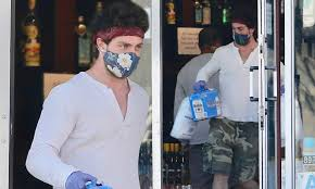 Aaron Taylor-Johnson wears a face mask, gloves and a bandana as he ...