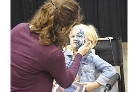 Slime squishes its way into Sarasota - Callie Smith, 6, gets her face  painted.   Your Observer