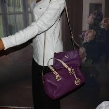 purple leather handbag with makeup bag