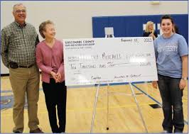 Hillary Mitchell (right) was announced as the winner of the Gasconade  County Math & Science Scholarship at the Hermann-Owensville boys'  basketball game at Hermann on Feb. 18. Presenting the award were Gerald