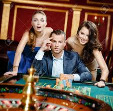Man With Two Women Playing Roulette At The Casino. Addiction ...