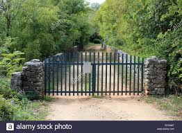Narrow Dirt Road Driveway Surrounded With Traditional Stone Wall And Dense Trees Closed With Blue Fence Metal Doors With Mounted Grey Mailbox Stock Photo Alamy