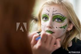 mother applying face paint makeup for