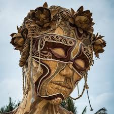 a towering wooden sculpture by daniel