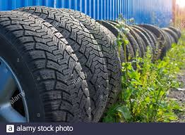 Sets Of Car Tires With Disks Are On The Street On The Ground Near The Fence Of The Cottage Against The Background Of Glare From The Sun Stock Photo Alamy