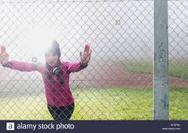 Young Woman Standing Behind Mesh Wire Fence Doing Stretching Exercises Stock Photo 276414977 Alamy