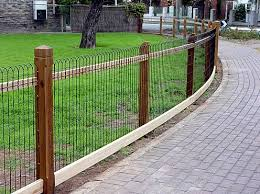 This Is A Nice Example Of Natural Wood Posts To Support Ornamental Woven Wire Fencing So That It Is Designed To Weathe Fence Design Backyard Fences Brick Fence