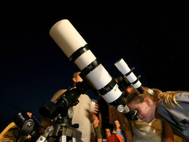 personas mirando las estrellas a través de un telescopio
