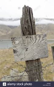 Old Wooden Fence Post With Remnants Of Barbed Fencing Wire And A Stock Photo Alamy