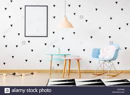 Mockup Of Poster On Wall In Bright Kid S Room With Geometric Carpet And Tables Next To Rocking Chair With White Pillow Stock Photo Alamy