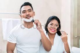 asian morning couple in bathroom stock