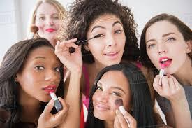 women applying makeup in mirror stock