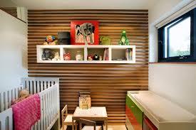 small nursery next to wood panel walls