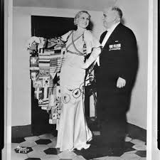 Peggy Hamilton, wearing an Olympics theme gown, with Governor James Rolph  at the Philharmonic Auditorium, Los Angeles, circa 1932 — Calisphere