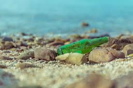 green bottle on the beach stock photo