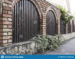Arched Wood Planks Brick And Stone Fence With Foliage Stock Photo Image Of Frame Brown 128807918