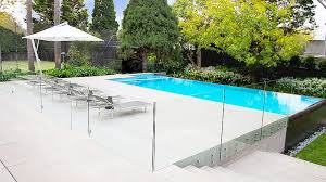 Pool And Spa With Blue Interior Tile And Infinity Edge Glass Pool Fence Fixed To Outside Of Wall Pinned To Pool Desi Glass Pool Fencing Glass Pool Pool Fence