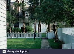 White Picket Fence On Garden With Brick Path And Newly Mown Lawn In Front Of Small White House Stock Photo Alamy