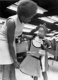 Leola Smith, of Dorchester, holds up a potential dress for a ...