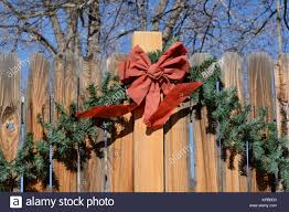 Red Christmas Bow And Green Leaves Decoration On Wooden Fence Stock Photo Alamy