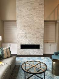 two story white stacked stone fireplace