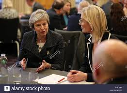 Prime Minister Theresa May meets Nora Smith, chief executive of CO3, and  Jonathan McAlpin of East Belfast Enterprise, at Queen's University in  Belfast, during her visit to Northern Ireland Stock Photo -