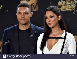 TV personality Trevor Noah (L) and singer Jordyn Taylor attend the MTV  Movie & TV Awards in the rain at the Shrine Auditorium in Los Angeles on  May 7, 2017. It will