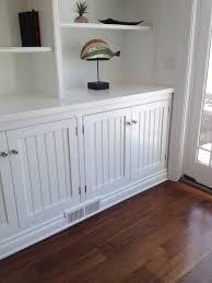 room has white beadboard cabinet doors