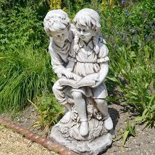 girl and boy reading a book garden statue
