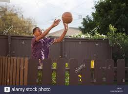 Boy Throwing Basketball Near Fence Stock Photo Alamy