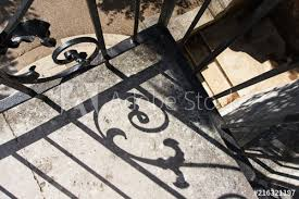 High Angle View Of Balcony With Decorative Cast Iron Fence Projecting Its Shadow On Its Surface Looking Down At The Formal Garden On The Ground Buy This Stock Photo And Explore