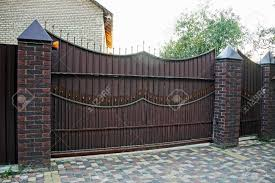 Gates And Wicket Of Brown Color On The Brick Fence In Front Of Stock Photo Picture And Royalty Free Image Image 83284223