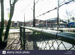 Chain Link Fence With Barbed Wire At The Top Encloses A Private Area Against A Blurred