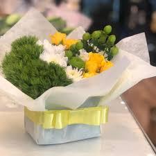 باقة ورد طبيعي ابيض وأصغر بشريط أصفر أنفاسك زهور