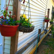 Simple Board Fence Posts With Hanging Baskets For Added Landscaping Along The Side Of The House Hanging Baskets Porch Swing Outdoor Decor