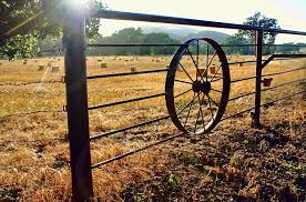 Sun Flare Over A Field Surrounded By A Metal Fence With A Wagon Wheel In It By Robin Keefe Photo Stock Snapwire