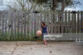 A Small Girl Dribbles A Basketball In A Driveway In Front Of Fence High Res Stock Photo Getty Images
