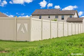 Tan Colored Vinyl Fence Surrounding A Homes Backyard Grass And Blue Sky In The Background Buy This Stock Photo And Explore Similar Images At Adobe Stock Adobe Stock