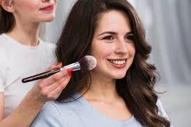 female makeup artist applying powder