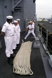 US Navy Boatswain's Mate 3rd Class Adrian Robles tosses a line ashore while  his crew of