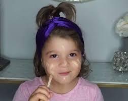 toddler applies full face of makeup for