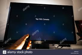 Paris, France - Circa 2019: Man hand holding remote control of Apple TV in  front of Panasonic Plasma tv set in living room with Top 100 Canada text on  Apple Music Stock Photo - Alamy